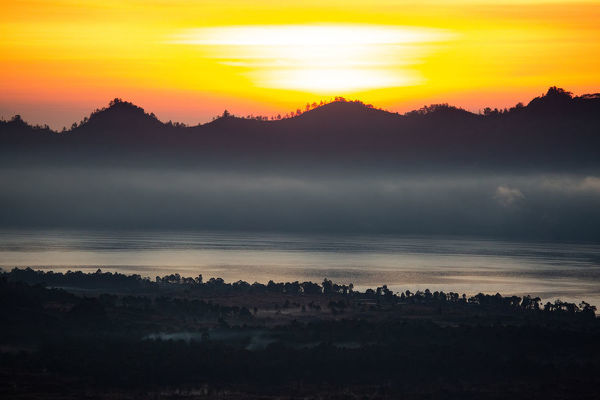 Sunrise over Mt Batur, a volcano in the Kintamani region of Bali. Golden colours and fog create a dramatic view of the Batur caldera lake and its surrounds