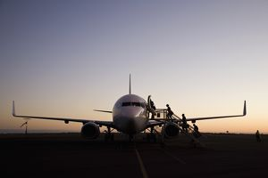 travel/western australia wa north west pilbara port hedland/people boarding airplane dusk port hedland western